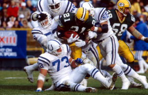 Indianapolis Colts linebackers Fredd Young (56) and Barry Krauss (55) and defensive tackle Joe Klecko (73) team up to stop Green Bay Packers running back Brent Fulwood (21) during an NFL game in Green Bay, Wis., November 13, 1988. The Colts defeated the Packers 20-13. (AP Photo/Vernon Biever)